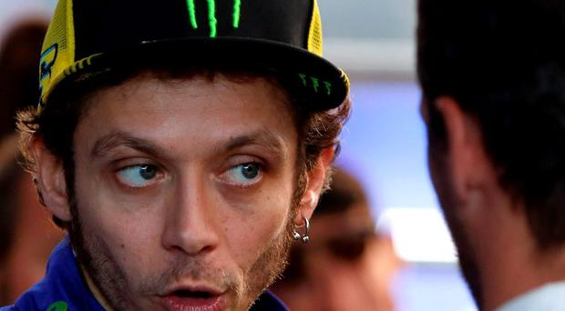 MotoGP rider Valentino Rossi of Italy speaks with team members at his box after the Valencia Motorcycle Grand Prix. (AP Photo/Alberto Saiz)