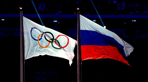 The Olympic flag flies next to the Russian flag