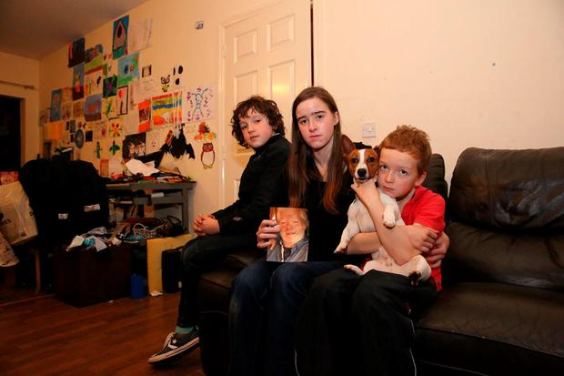 Claire-Marie Malone, with her sons Fionn (9) and Cormac (7), holds a photo of her late ex-partner Michael Gallagher. Photo: Mary Browne