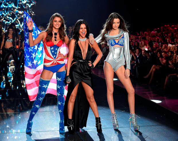 Model and new Victoria's Secret Angel Taylor Hill from Illinois (L) and model Megan Puleri from Ohio (R) walk the runway while singer Selena Gomez performs during the 2015 Victoria's Secret Fashion Show at Lexington Avenue Armory on November 10, 2015 in New York City. (Photo by Dimitrios Kambouris/Getty Images for Victoria's Secret)