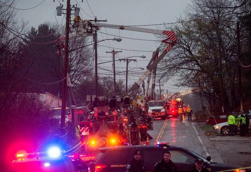 Emergency personnel and electrical crews work at the scene where authorities say a small business jet crashed into an apartment building in Akron, Ohio, Tuesday, Nov. 10, 2015. (AP Photo/Phil Long)