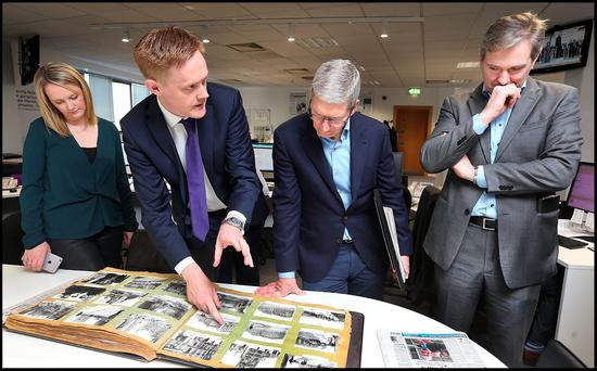 Fionnán Sheahan, Editor of the Irish Independent, with Mr Rae, shows Mr Cook some historic photographs from 1916