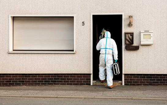 A police investigator in protective cloth enter a house in Wallenfels, southern Germany, Friday morning, Nov. 13, 2015 where police found bodies of multiple babies