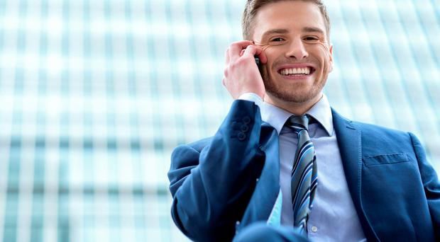 Happy businessman using cell phone outside office
