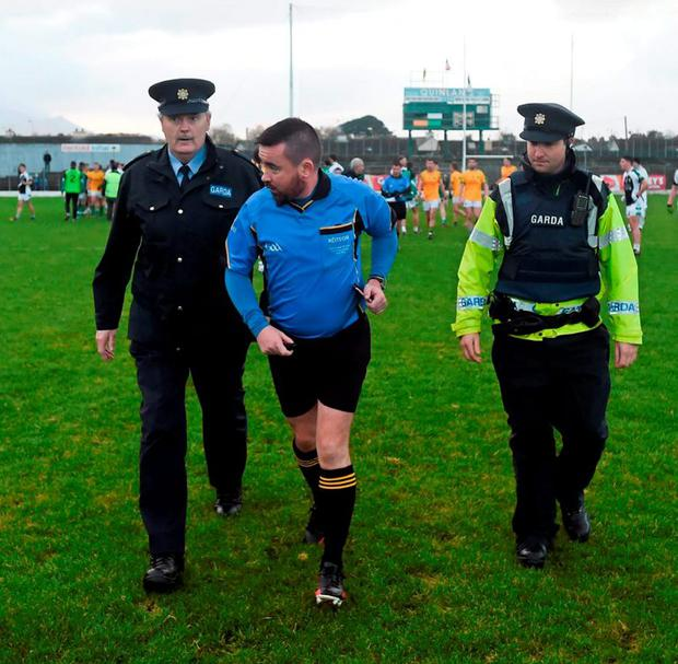 Referee Seamus Mulvihill is escorted from the pitch after the game
