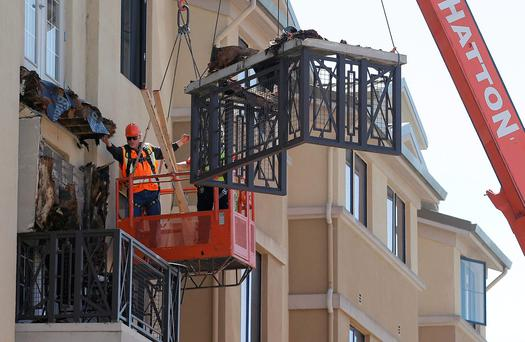 Workers remove part of a balcony that collapsed at the Library Gardens apartment complex in Berkeley