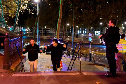 Two men evacuate the Place de la Republique square in Paris as a police officer looks on, after several shootings. Photo: AFP/Getty Images