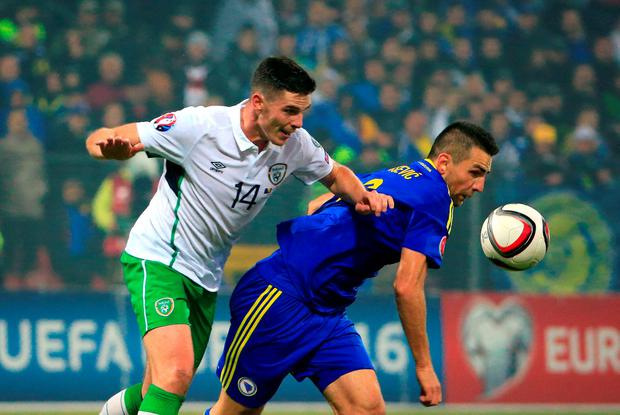 Vedad Ibisevic (R) of Bosnia is challenged by Ciaran Clark