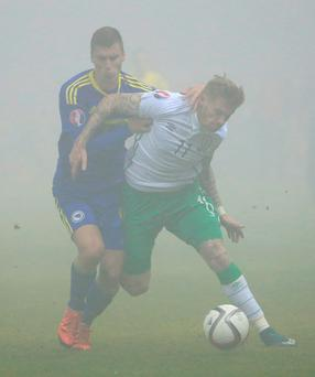 Ireland's James McClean battles the fog and Bosnia's Ognjen Vranjes