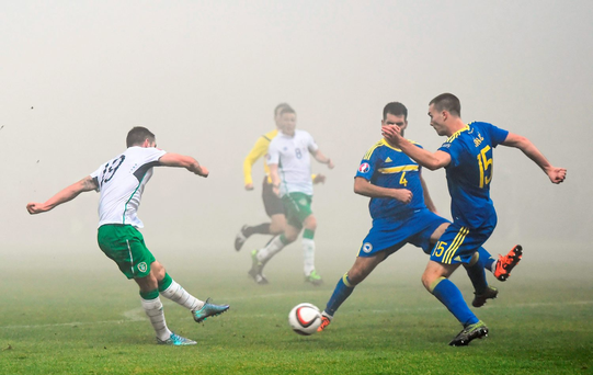 Robbie Brady fires his shot through the legs of the Bosnian defence - and the fog - to give Ireland the lead