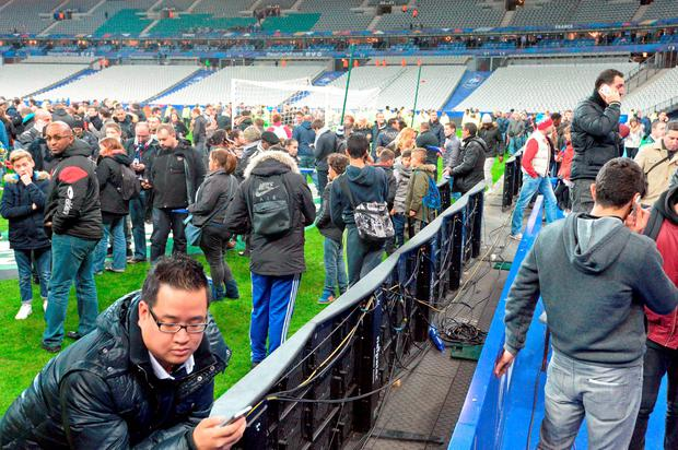 Spectators wait on the pitch of the Stade de France stadium following the friendly football match between France and Germany in Saint-Denis, north of Paris, on November 13, 2015, after a series of gun attacks occurred across Paris as well as explosions outside the national stadium where France was hosting Germany. At least 18 people were killed, with at least 15 people had been killed at the Bataclan concert hall in central Paris, only around 200 metres from the former offices of Charlie Hebdo which were attacked by jihadists in January. AFP PHOTO / MIGUEL MEDINAMIGUEL MEDINA/AFP/Getty Images