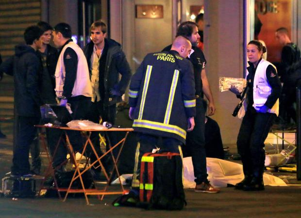 Rescue workers at the scene as victims lay on the pavement outside a Paris restaurant. Photo: AP