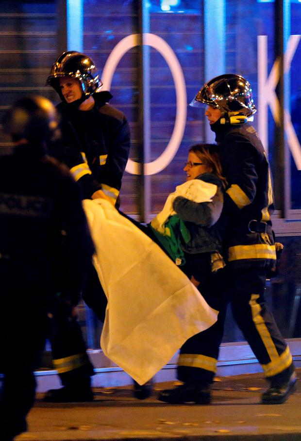 French fire brigade members aid an injured individual near the Bataclan concert hall following fatal shootings in Paris, France, November 13, 2015. At least 30 people were killed in attacks in Paris and a hostage situation was under way at the concert hall in the French capital, French media reported on Friday. REUTERS/Christian Hartmann