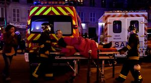 Rescuers workers evacuate a man on a stretcher near the Bataclan concert hall in central Paris. Photo: AFP/Getty Images
