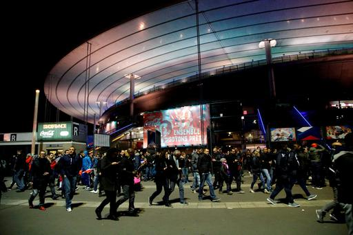 People leave the Stade de France stadium after the international friendly soccer France against Germany, Friday, Nov. 13, 2015 in Saint Denis, outside Paris. Two police officials say at least 11 people have been killed in shootouts and other violence around Paris. Police have reported shootouts in at least two restaurants in Paris. At least two explosions have been heard near the Stade de France stadium, and French media is reporting of a hostage-taking in the capital. (AP Photo/Michel Euler)