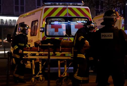 Rescue workers evacuate a woman near the Bataclan concert hall in central Paris, on November 13, 2015.