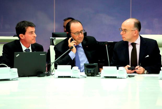 A handout picture taken and released on November 13, 2015 by the Presidence of the Republique shows (from L) French Prime Minister Manuel Valls, French President Francois Hollande and French Interior Minister Bernard Cazeneuve, attending an emergency meeting at the Interior Minister on November 13, 2015, after several attacks in Paris. AFP PHOTO / PRESIDENCE DE LA REPUBLIQUE / CHRISTELLE ALIX