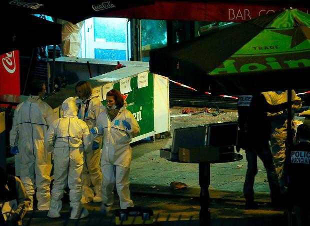 Investigators work outside a bar near the Stade de France where explosions were reported to have detonated outside the stadium during the France vs German friendly soccer match near Paris, November 13, 2015. REUTERS/Gonazlo Fuentes