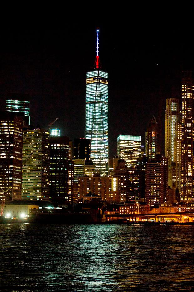 The One World Trade Center spire is lit blue, white and red after New York Gov. Andrew Cuomo announced the lighting in honor of dozens killed in the Paris attacks Friday, Nov. 13, 2015, in New York. French officials say several dozen people have been killed in shootings and explosions at a theater, restaurant and elsewhere in Paris. (AP Photo/Kevin Hagen)