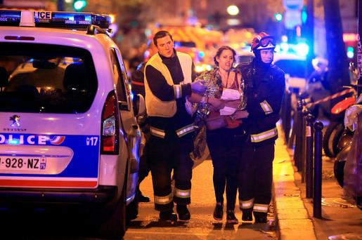 Rescue workers help a woman after a shooting, outside the Bataclan theater in Paris, Friday Nov. 13, 2015. French President Francois Hollande declared a state of emergency and announced that he was closing the country's borders. (AP Photo/Thibault Camus)