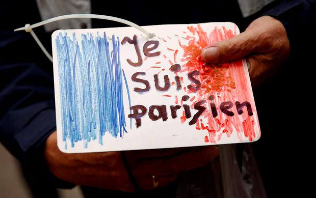 A man holds a drawing depicting the French flag and carrying the words