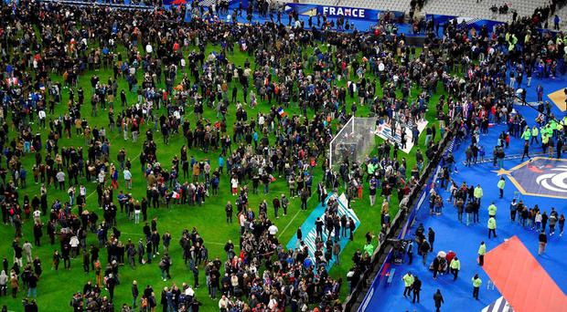 Football fans gather on the field of the Stade de France stadium following the friendly football match between France and Germany in Saint-Denis last night