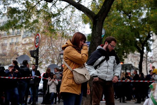 A woman looks at messages and flowers left at a rail cordon close to the Bataclan theatre in the 11th district of Paris on November 14, 2015, the day after a series of attack on the city resulting in the deaths of more than 128 individuals. Some 80 people were gunned down at the Bataclan theatre in Paris late November 13, during a concert by the US band Eagles of Death Metal. AFP PHOTO / KENZO TRIBOUILLARDKENZO TRIBOUILLARD/AFP/Getty Images