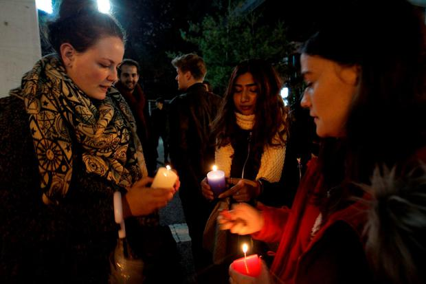 SEOUL, SOUTH KOREA - NOVEMBER 14: Members of the French community living in South Korea light candles at a vigil outside the French embassy on November 14, 2015 in Seoul, South Korea. At least 128 people were killed in a series of bombings and shootings across Paris, including at a soccer game at the Stade de France and a concert at the Bataclan theater. (Photo by Chung Sung-Jun/Getty Images)