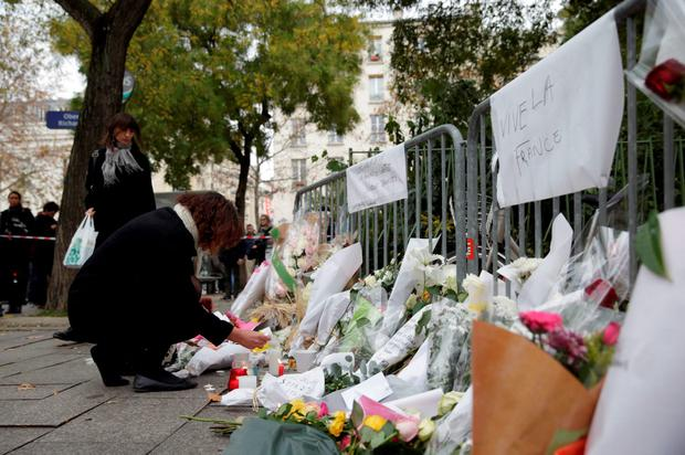 A woman lays a bunch of flowers at a rail cordon close to the Bataclan theatre in the 11th district of Paris on November 14, 2015, the day after a series of attack on the city resulting in the deaths of more than 128 individuals. Some 80 people were gunned down at the Bataclan theatre in Paris late November 13, during a concert by the US band Eagles of Death Metal. AFP PHOTO / KENZO TRIBOUILLARDKENZO TRIBOUILLARD/AFP/Getty Images