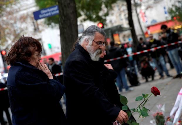 People lay flowers at a rail cordon close to the Bataclan theatre in the 11th district of Paris on November 14, 2015, the day after a series of attack on the city resulting in the deaths of more than 128 individuals. Some 80 people were gunned down at the Bataclan theatre in Paris late November 13, during a concert by the US band Eagles of Death Metal. AFP PHOTO / KENZO TRIBOUILLARDKENZO TRIBOUILLARD/AFP/Getty Images