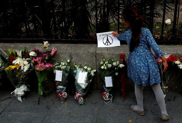 A girl places a paper, carrying a peace sign featuring Eiffel Tower, next to candles and flowers in memory of victims of deadly attacks in Paris, outside the French embassy in Madrid, Spain, November 14, 2015. REUTERS/Sergio Perez