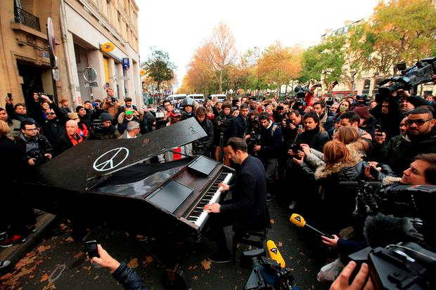 An unnamed man brings his portable grand piano and plays John Lennon's Imagine by the Bataclan, one of the venues for the attacks in the French capital Credit: John Walton/PA Wire