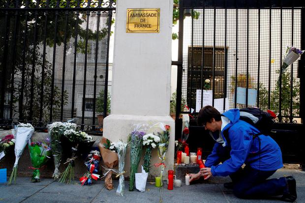 A woman lights a candle next to flowers placed in memory of victims of deadly attacks in Paris, outside the French embassy in Madrid, Spain, November 14, 2015. The papers read in French,