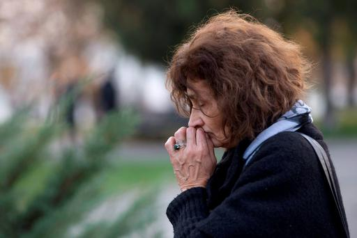 A woman cries in front of the Monument of Gratitude to France after she lighted a candle for the victims of the attacks in Paris, in Belgrade, Serbia, November 14, 2015.