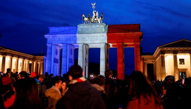 People stand in front of the Brandenburg gate in Berlin, which is illuminated in blue, white and red in the colors of the French flag in tribute to victims of Friday's attacks in Paris REUTERS/Hannibal Hanschke