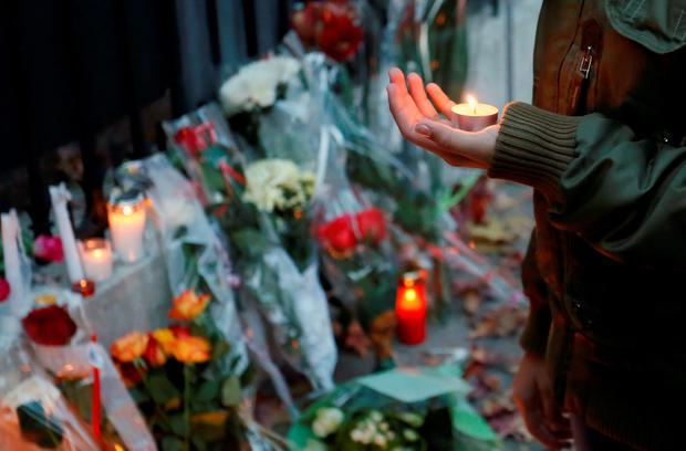 A woman holds a candle during a ceremony honoring victims of the attacks in Paris, outside the Consulate of France in Geneva, Switzerland, November 14, 2015. REUTERS/Pierre Albouy