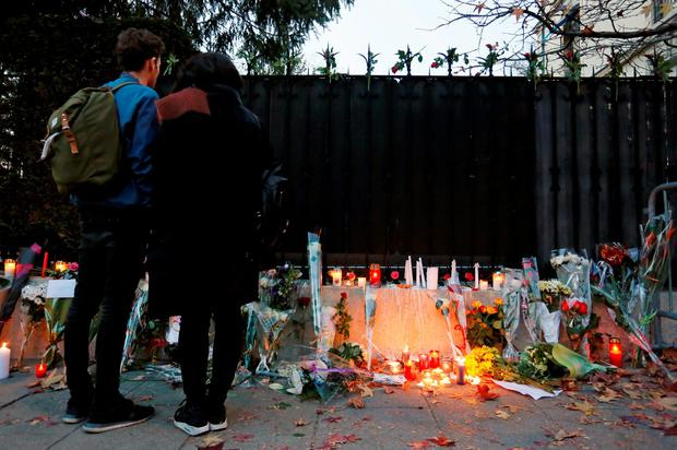 People stand in front of a memorial as they honor victims of the attacks in Paris, outside the Consulate of France in Geneva, Switzerland, November 14, 2015. REUTERS/Pierre Albouy
