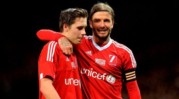 Great Britain & Ireland's David and Brooklyn Beckham (left) during the UNICEF charity match at Old Trafford, Manchester. PRESS ASSOCIATION Photo. Picture date: Saturday November 14, 2015. See PA story SOCCER UNICEF. Photo credit should read: Martin Rickett/PA Wire.