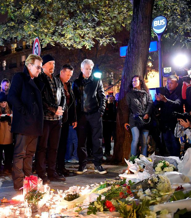 Irish band U2 (From L) lead singer Bono, guitarist The Edge, drummer Larry Mullen Jr and bass player Adam Clayton pay homage to attacks victims near the Bataclan concert hall on November 14, 2015 in Paris, AFP PHOTO / FRANCK FIFEFRANCK FIFE/AFP/Getty Images