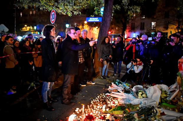 PARIS, FRANCE - NOVEMBER 14: Bono and The Edge of U2 place flowers on the pavement near the scene of yesterday's Bataclan Theatre terrorist attack on November 14, 2015 in Paris, France. At least 120 people have been killed and over 200 injured, 80 of which seriously, following a series of terrorist attacks in the French capital. (Photo by Jeff J Mitchell/Getty Images)