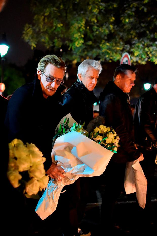 PARIS, FRANCE - NOVEMBER 14: Bono and band members of U2 place flowers on the pavement near the scene of yesterday's Bataclan Theatre terrorist attack on November 14, 2015 in Paris, France. At least 120 people have been killed and over 200 injured, 80 of which seriously, following a series of terrorist attacks in the French capital. (Photo by Jeff J Mitchell/Getty Images)