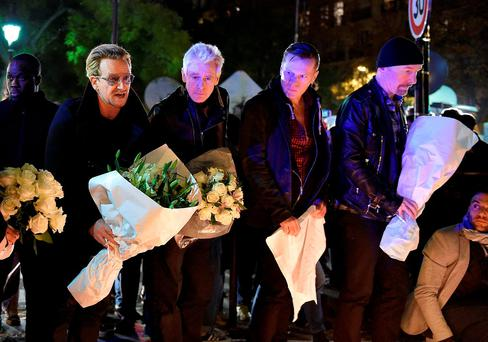 Irish band U2 (From L) lead singer Bono, bass player Adam Clayton, drummer Larry Mullen Jr and guitarist The Edge pay homage to attacks' victims near the Bataclan concert hall on November 14, 2015 in Paris AFP PHOTO / FRANCK FIFEFRANCK FIFE/AFP/Getty Images