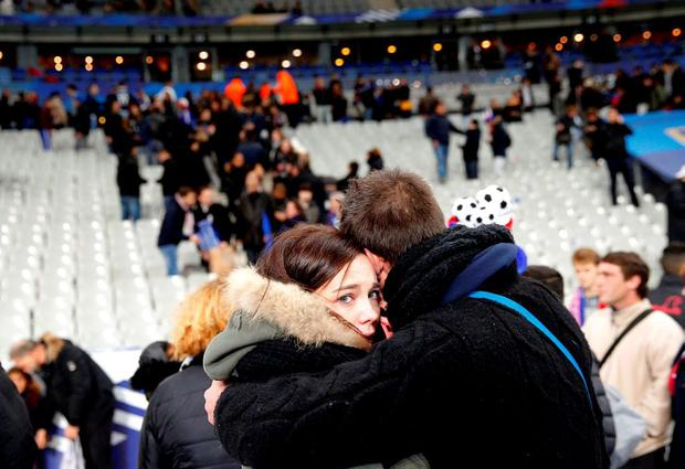 Spectators embrace each other as they stand on the playing field of the Stade de France stadium at the end of a friendly soccer match between France and Germany in Saint Denis, outside Paris yesterday. Hundreds made their way to the pitch after explosions were heard nearby. Multiple fatal attacks throughout the city have prompted President Francois Hollande to announce he was closing the country's borders and declaring a state of emergency. (AP Photo/Christophe Ena)