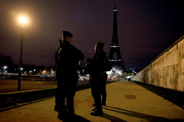 Police officers stand guard near the Eiffel Tower which has its lights turned off on November 14, 2015 following the deadly attacks in Paris. Islamic State jihadists claimed a series of coordinated attacks by gunmen and suicide bombers in Paris that killed at least 129 people in scenes of carnage at a concert hall, restaurants and the national stadium. AFP PHOTO / ALAIN JOCARDALAIN JOCARD/AFP/Getty Images