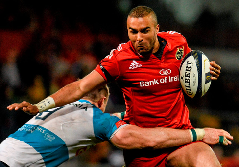Munster's Simon Zebo tries to evade a tackle by Marco Barbini