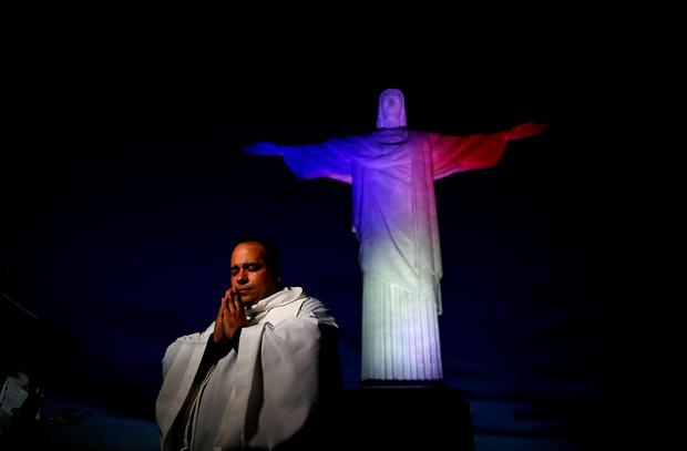 A priest gestures during an event in tribute to the victims of Paris attacks, as the Christ the Redeemer is lit up in France's official colours in Rio de Janeiro, Brazil, November 14, 2015. REUTERS/Pilar Olivares