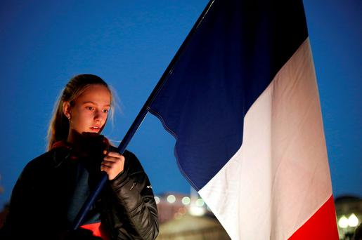 A girl holds a French flag during a vigil for the victims of the Paris attacks, outside the White House in Washington November 14, 2015. REUTERS/Yuri Gripas