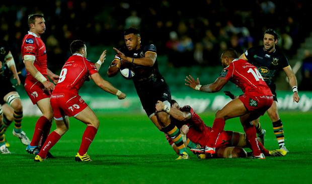 Northampton Saints' Luther Burrell (centre) is tackled by Scarlets' Gareth Davies (left) and Michael Tagicakibau (No.14) during the match