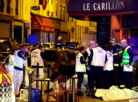 NIGHT OF FEAR: Rescue service personnel work near the covered bodies outside Le Carillon where 14 people were murdered