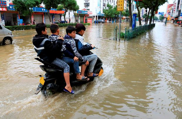 Residents ride a motorcycle along a flooded street after heavy rainfall in Hezhou, Guangxi Zhuang Autonomous Region